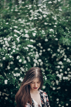 hipster woman with  sunglasses posing on background of blooming bush with white flowers of spirea. boho girl sensual portrait in floral clothes. space for text. spring summer time
