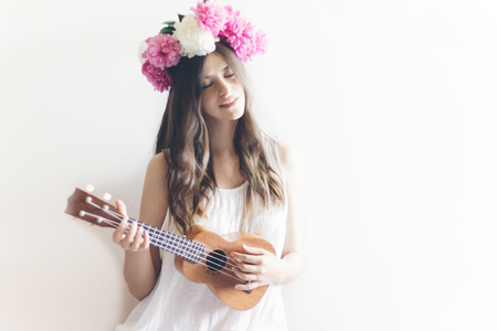 hipster woman playing ukulele, posing in peonies wreath and in white dress. romantic boho bride with peony crown holding guitar, relaxing moment, space for text. sensual hawaii girl portrait
