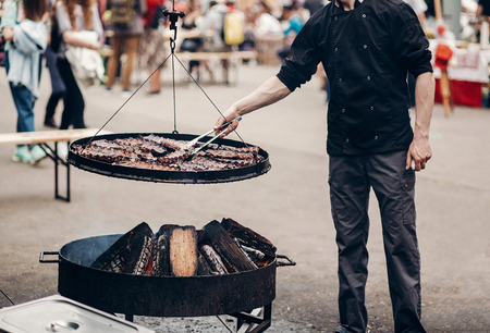 grilled meat. man holding steel tongues and roasting beef pork on big grill, under wooden fire. chef in black form cooking smoked juicy ribs. street food festival. summer picnic Archivio Fotografico