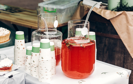 big glass jar with strawberry orange lemonade and paper cups, space for text. street food festival. drink bar at reception, catering outdoors. summer picnic. colorful drinks 版權商用圖片