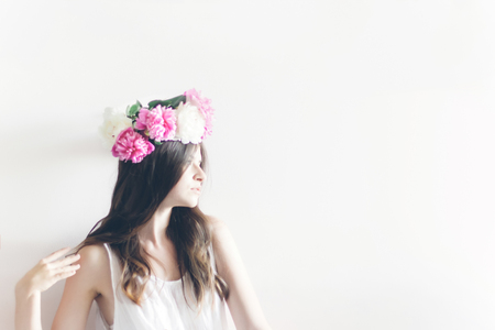 hipster woman with peonies wreath and in white dress posing in white room. romantic boho bride with peony crown, relaxing in morning, space for text. sensual girl portrait