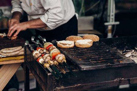 grilling barbecue kebab on skewers. meat and vegetables and bread buns roasting on grill. man roasting meat. chef in form cooking smoked juicy beef pork. street food festival. Stockfoto