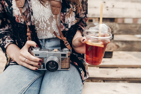 stylish hipster woman holding old photo camera and lemonade. boho girl in denim and bohemian clothes, sitting on wooden bench at street food festival. summer travel. space for text