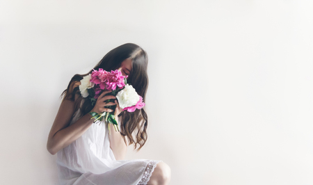 hipster woman in white dress holding pink bouquet of peonies in white room. boho bride with peony bouquet in front, relaxing in morning, space for text. spring girl with flowers