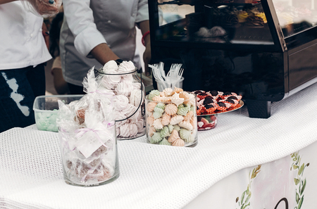 colorful desserts meringue and whipped cream cookies on table at street food festival. candy bar with tasty sweets cakes, catering at wedding reception. summer picnic