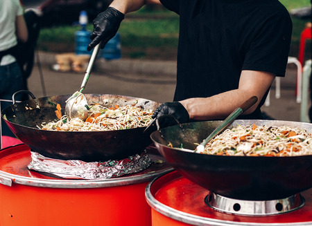 man stiring pasta with vegetables and seafood at street food festival. chef with gloves  cooking traditional italian macaroni dish. open kitchen outdoors, catering. summer picnic