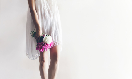 peony bouquet in hand. hipster woman in white dress holding pink bouquet of peonies in white room. boho bride relaxing in morning, space for text