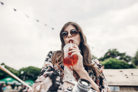 stylish hipster woman drinking lemonade. cool boho girl in denim and bohemian clothes, with cocktail and old camera sitting on wooden bench at street food festival. summertime Stockfoto