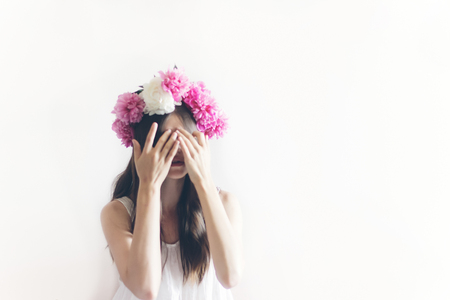 hipster woman with peonies wreath and in white dress posing in white room, hiding face with hands. sensual boho bride with peony crown, relaxing in morning, space for text.