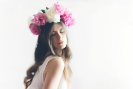 blurred image of hipster woman with peonies wreath and in white dress posing in white room. romantic boho bride with peony crown in morning, space for text. sensual girl background