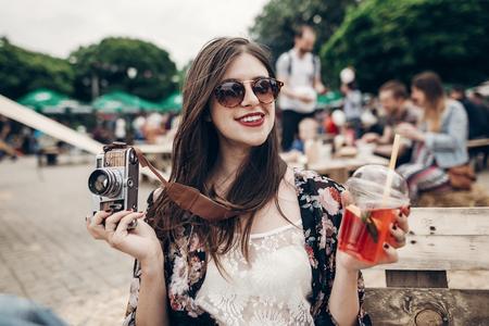 Stijlvolle hipster vrouw in zonnebril met rode lippen die limonade en oude fotocamera houden. Boho Girl Holding Cocktail en lachen op Street Food Festival. zomer. zomervakantie