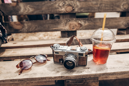 sunglasses camera and lemonade cup on wooden background at summer street food festival. space for text. summer travel, wanderlust concept. hello summer. hipster food set Stockfoto