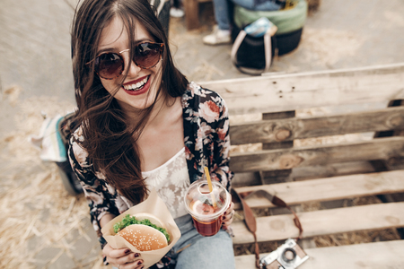 stylish hipster woman holding juicy burger and lemonade. boho girl holding  cheeseburger and smiling at street food festival. summertime. summer vacation travel. space for text Stockfoto