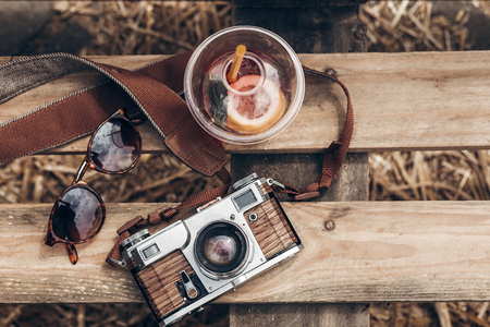 lemonade sunglasses camera on wooden background at summer street food festival flat lay. space for text. summer travel, wanderlust concept. hello summer vacation top view. hipster set Archivio Fotografico