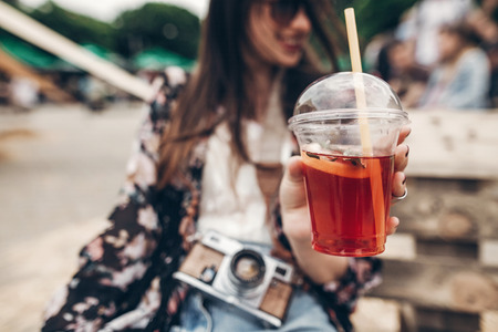 lemonade in hand. happy stylish hipster woman holding lemonade. cool boho girl in denim and bohemian clothes, with cocktail and camera at street food festival. summertime. summer vacation