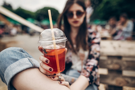 strawberry lemonade in hand. stylish hipster woman in sunglasses with red lips holding lemonade. cool boho girl with cocktail at street food festival. summertime. summer vacation travel