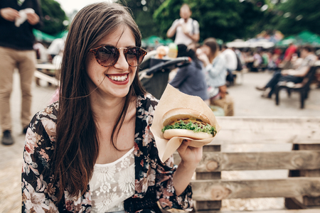 stylish hipster woman in sunglasses with red lips holding juicy burger. boho girl holding  hamburger and smiling at street food festival. summertime. summer vacation travel Stockfoto