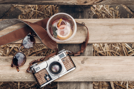 hello summer vacation top view. lemonade sunglasses camera on rustic wooden background at summer street food festival flat lay. space for text. summer travel, wanderlust concept.
