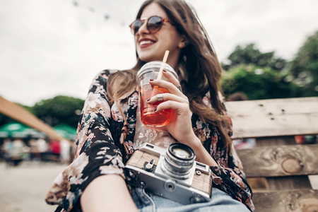 happy stylish hipster woman holding lemonade. cool boho girl in denim and bohemian clothes, with cocktail and old camera at street food festival. summer vacation travel