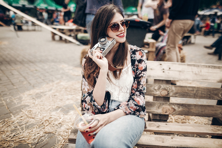 stylish hipster woman in sunglasses with red lips holding lemonade and old photo camera. boho girl holding cocktail and smiling at street food festival. summer  vacation. space for text
