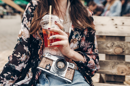 stylish hipster woman holding lemonade. cool boho girl in denim and bohemian clothes, with cocktail and old camera at street food festival. summer vacation travel