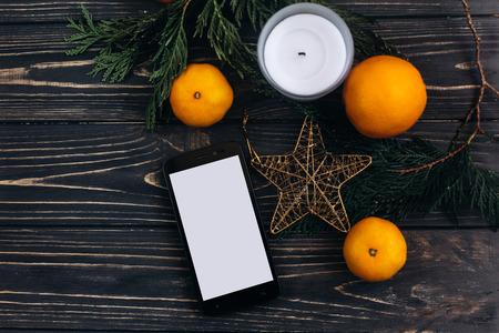Kerst reclame concept telefoon met leeg scherm op Kerstmis achtergrond van groene takken en sinaasappelen en gouden ster op zwarte rustieke houten bureau. plat leggen. ruimte voor tekst