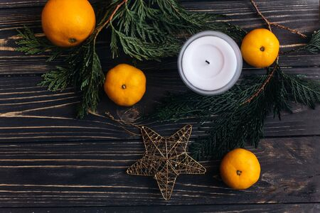 stylish christmas flat lay with green branches and oranges and golden star on black rustic wooden background. seasonal greeting and shopping advertising concept. space for text