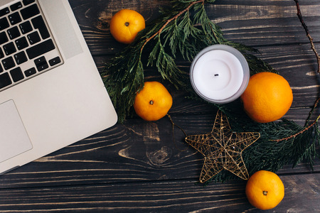 christmas flat lay of laptop and green branches and oranges and golden star on black rustic wooden desk. space for text. advertising concept