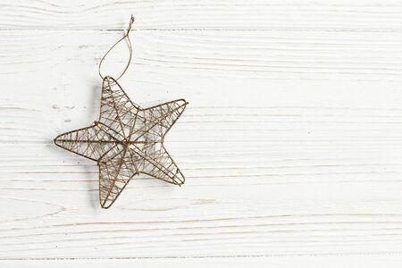 christmas golden star on stylish white rustic wooden background. space for text. holiday greeting card concept. unusual creative top view