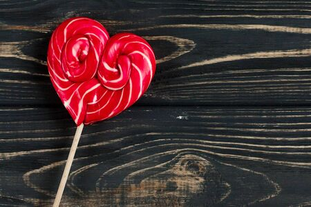 shiny black: heart candy lollipop on stylish black rustic wooden background. space for text. happy valentines day concept. holiday greeting card concept. unusual creative top view