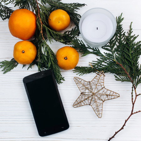 stylish christmas flat lay. phone with empty screen and oranges and golden star on white rustic wooden background. seasonal greeting and shopping advertising concept. space text