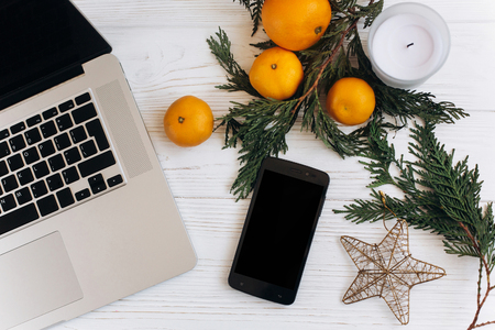 stylish christmas flat lay. laptop and phone with empty screen on white wooden background with seasonal ornaments of oranges and golden star. advertising concept