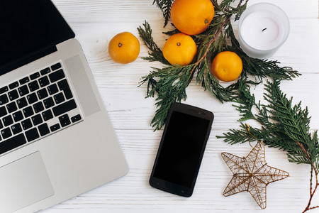 stylish laptop and phone with empty screen on white wooden background with christmas oranges and golden star and candle. flat lay. seasonal advertising concept