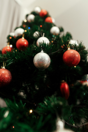 close up of colorful red and silver christmas ornaments on christmas tree with lights