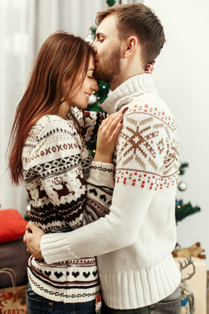 stylish happy couple sensually kissing at christmas tree. joyful cozy moments in winter holidays. seasonal greetings. advertising concept with space for text.