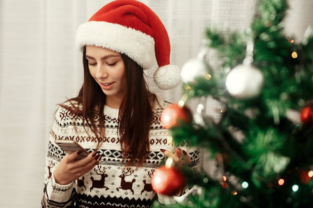 stylish woman holding phone looking at screen at christmas tree lights. wearing sweater reindeers and santa hat smiling. seasonal greetings concept. space for text