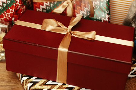 luxury big red present box with golden ribbon on background of stacked stylish gifts under beautiful christmas tree in room. seasonal greetings concept. space for text.