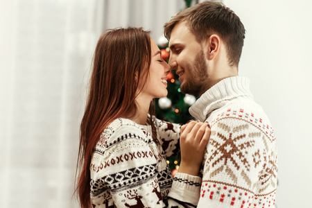 stylish happy family gently hugging at christmas tree. joyful cozy moments in winter holidays. seasonal greetings. advertising concept with space for text. Stock Photo