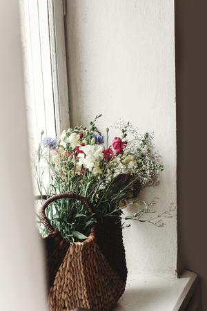 籐バッグ素朴な白いウィンドウ上で野生の花。日光、テキスト用のスペースで茶色のバスケットにカラフルな花。田園大気瞬間。珍しい夏の写真
