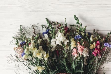 prachtige wilde bloemen in rieten tas op rustieke witte houten achtergrond. kleurrijke bloemen in de mand in licht, ruimte voor tekst. rustieke bruiloft concept, plat lag, landelijke zomer foto Stockfoto