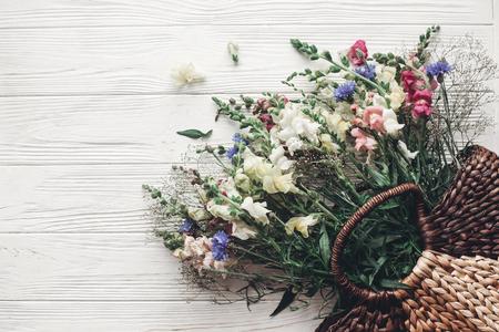 Lindas flores silvestres em saco de vime no rústico de madeira branco fundo plana leigos. flores coloridas na cesta de luz, espaço para texto, vista superior. momento atmosférico rural. imagens de verão Foto de archivo - 84113364