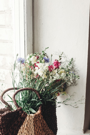 wildflowers in wicker bag on rustic white window. colorful flowers in brown basket in sunlight, space for text. rural atmospheric moment. unusual summer picture
