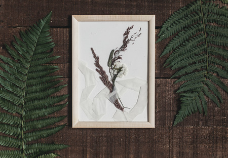 rustic boutonniere under glass in frame on wooden rustic background with fern leaves. barn wedding concept. top view. Stock Photo