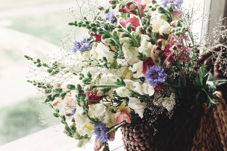 beautiful wildflowers in wicker bag on rustic white window. colorful flowers in brown basket in sunlight, space for text. rural atmospheric moment. rustic wedding, mother woman day