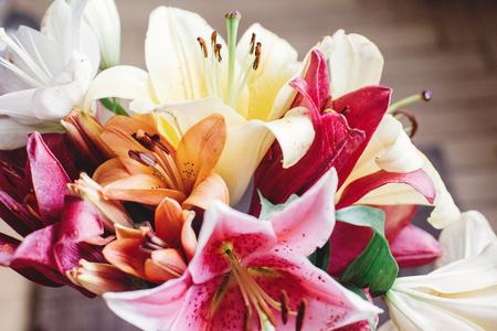 素朴な木製の背景に美しいカラフルなユリの花束。素朴な木製の背景にゴージャスな花ユリ。テキストのためのスペース。グリーティング カード。