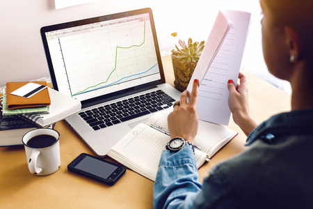 stylish young hipster girl working economist financial analytics holding pen on craft background with laptop and papers Stock Photo