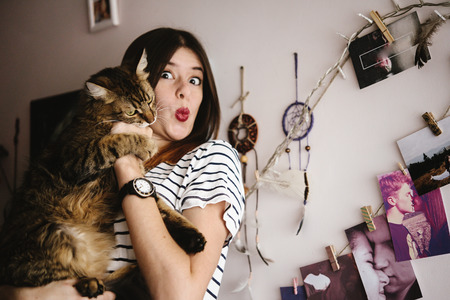 stylish hipster woman playing with her cat in modern room