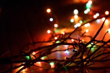 stylish retro christmas garland lights on wood branches, holiday celebration concept