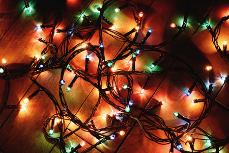 stylish retro christmas garland lights on wood branches, holiday celebration concept
