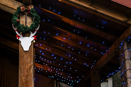 stylish christmas deer and wreath and garland lights , celebration decoration for holidays in the city